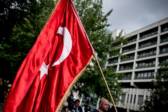 epa06879749 A man holds a Turkish flag in front of the Higher Regional Court (Oberlandesgericht OLG) in Munich, Bavaria, Germany, 11 July 2018. The court found Beate Zschaepe guilty on ten counts of murder on 11 July 2018, some five years after the trial started. The court sentenced her to life imprisonment and established the particular severity of guilt. Zschaepe was accused of being a founding member of the extreme right-wing National Socialist Underground (NSU) terror cell and faced charges of complicity in the murder of nine Turkish and Greek immigrants and a policewoman between 2000 and 2007, as well as two bombings in immigrant areas of Cologne, and 15 bank robberies.  EPA/FILIP SINGER