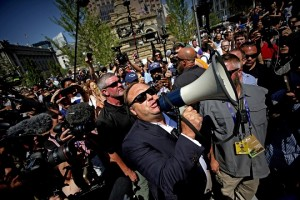epa06913532 (FILE) - US radio host Alex Jones (C) uses a megaphone to speak to crowds near the Quicken Loans Arena, the venue for the 2016 Republican National Convention (RNC), in Cleveland, Ohio, USA, 19 July 2016 (reissued 27 July 2018). US video-sharing and streaming service YouTube on 26 July 2018 banned controversial right-wing conspiracy theorist Alex Jones and his channel Inforwars for 90 days. YouTube said the channel was violating its 'policies against child endagerment and hate speech'.  EPA/BRIAN BLANCO *** Local Caption *** 52901715