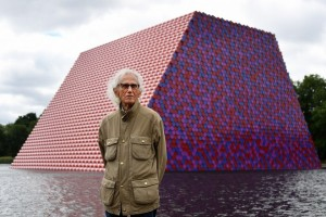 epa06818992 Bulgarian artist Christo stands in front of his artwork 'Mastaba' built on The Serpentine lake in London, Britain, 18 June 2018. Christo has unveiled his enormous floating structure in Hyde Park, which reaches more than 20 meters (65 feet) in height and comprises of 7,506 horizontally stacked barrels. It is Christo's first major public outdoor work in Britain.  EPA/ANDY RAIN