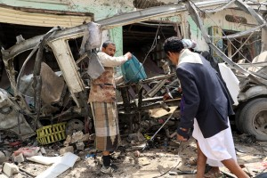 epa06940626 A Yemeni holds a schoolbag near a destroyed bus at the site of a Saudi-led airstrike a day after it hit the bus which was carrying children at a market in the northern province of Saada, Yemen, 10 August 2018. According to reports, an alleged Saudi-led airstrike hit a bus carrying children in a market in the northern Yemeni province of Saada, killing at least 50 people, mostly children, and wounding over 70 others.  EPA/STRINGER