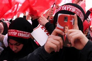 epa05896688 A supporter holds a smart phone with picture of Turkish President Recep Tayyip Erdogan as supporters of Erdogan cheer during a 'Vote Yes' rally in Istanbul, Turkey, 08 April 2017. A referendum on the constitutional reform in Turkey will be held on 16 April. The reform, passed by Turkish parliament on 21 January, would change the country's parliamentarian system of governance into a presidential one, which the opposition denounced as giving more power to Turkish president Recep Tayyip Erdogan.  EPA/SEDAT SUNA