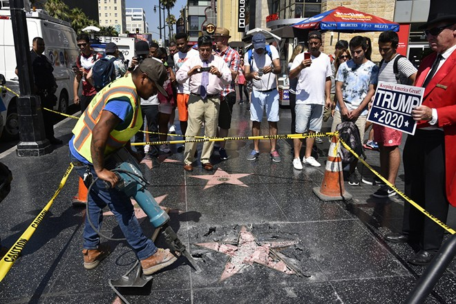 epa06910403 Workers remove the damaged remains of President Donald J. Trump's star on the Hollywood Walk of Fame after it was destroyed overnight in Hollywood section of Los Angeles, California, USA, 25 July 2018.  A suspect is in custody by Los Angeles Police Department.  EPA/BOB RIHA JR