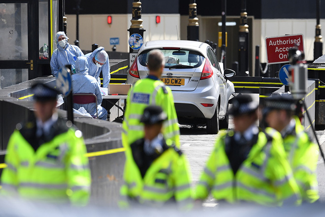 epa06949324 Forensics officers at work in front of the vehicle that crashed outside the Houses of Parliament in Westminster, London, Britain 14 August. A number of people have been injured after a car crashed into security barriers outside the Houses of Parliament on 14 August 2018, Scotland Yard said. The driver, a man in his late 20s, was arrested at the scece. Authorities said that the incident was treated as terror related and an investigation by the counter terrorism command was underway.  EPA/ANDY RAIN