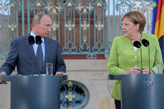 epa06957166 Russian President Vladimir Putin (L) and German Chancellor Angela Merkel (R) hold a joint news conference prior to their talks at the German government's guest house Meseberg Palace in Gransee near Berlin, Germany, 18 August 2018. Vladimir Putin pays a working visit to Germany to discuss the development of German-Russian relations as well as international issues.  EPA/ALEXEI DRUZHININ / SPUTNIK / KREMLIN POOL