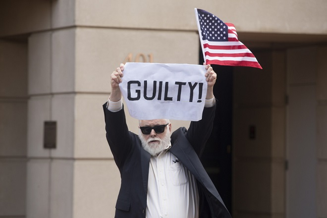 epa06963176 A man holds up a sign as people react to the first verdict in the trial of former Trump campaign charman Paul Manafort, at the US District Court in Alexandria, Virginia, USA, 21 August 2018. Manafort who was facing 18 charges including tax evasion and bank fraud was found guilty on 8 charges and the judge declared a mistrial on 10 other charges.  EPA/MICHAEL REYNOLDS
