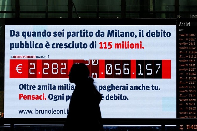 "A woman walks past a ""debt clock"" screen, installed by Bruno Leoni Institute's analysts, displaying Italy's public debt at the Termini central station in Rome, Italy February 15, 2018. REUTERS/Alessandro Bianchi"