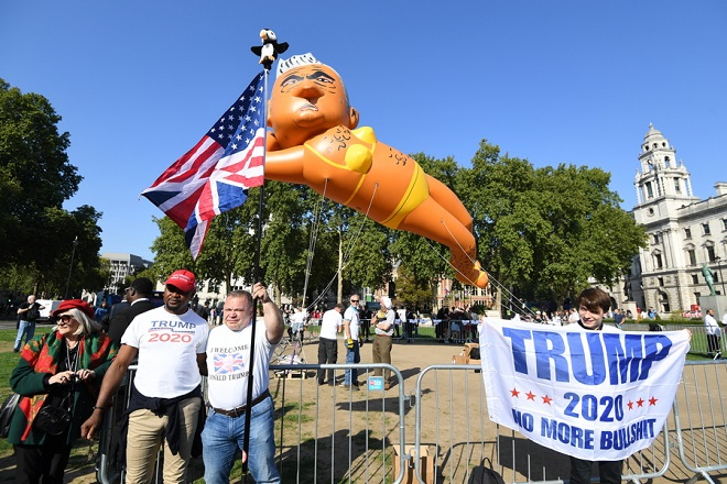 epa06989594 Supporters of US President Donald Trump pose next to an inflated blimp depicting the Mayor of London, Sadiq Khan, launched over the Parliament Square, in Westminster, London, Britain, 01 September 2018. Demonstrators were calling for the removal of Khan from his post. The 'Sadiq Khan in a bikini' blimp action is alleged to be as revenge after Mayor of London Khan approved the flying of the 20ft balloon resembling US President Trump during his visit to the UK.  EPA/FACUNDO ARRIZABALAGA