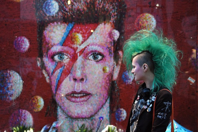 epa05709716 A fan stands next to a mural portrait of British musician David Bowie on the first anniversary of his death, in Brixton, London, Britain 10 January 2017. Bowie would have turned 70 on 08 January 2017. He died on 10 January 2016 after a battle with cancer.  EPA/FACUNDO ARRIZABALAGA