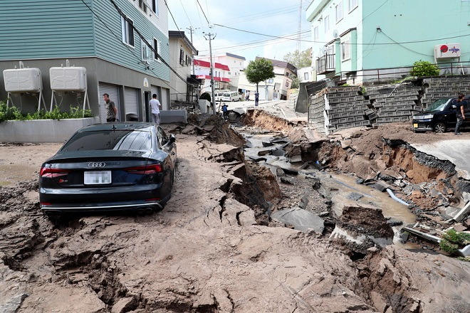 epa07000036 A mud covered car sits in the middle of a destroyed street following a powerful earthquake in Sapporo, Hokkaido, northern Japan, 06 September 2018. According to the Japan Meteorological Agency, a strong earthquake of 6.7 magnitude jolted Japan's northern island of Hokkaido in the early hours of 06 September causing large landslides and blackouts. A blackout over Hokkaido is affecting almost 3 million households.  EPA/JIJI PRESS JAPAN OUT EDITORIAL USE ONLY/  NO ARCHIVES