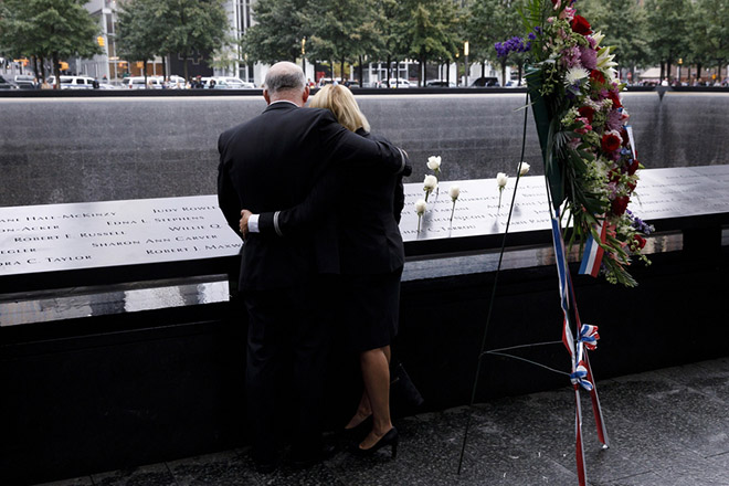 epa07012627 People embrace at South pool of the 9/11 Memorial during ceremonies marking the 17th anniversary of terrorist attacks in New York, New York, USA, 11 September 2018.  EPA/JUSTIN LANE