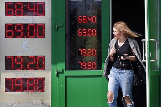 epa06966496 A woman leaves exchange office with an electronic panel displaying currency exchange rates for US dollar and euro against Russian ruble in Moscow, Russia, 23 August 2018. Russian ruble declined against dollar and euro on anticipation of escalating US sanctions.  EPA/YURI KOCHETKOV