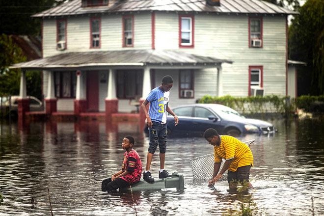 epa07023450 Three boys play in floodwaters after Hurricane Florence tore through New Bern, North Carolina USA, 15 September 2018. Florence has been downgraded to a tropical storm but is still expected to bring a storm surge with heavy flooding to the Carolinas.  EPA/JIM LO SCALZO