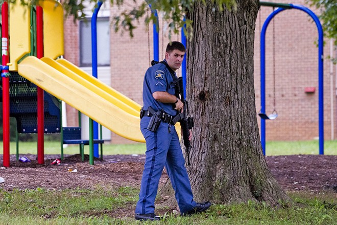 epa07034983 A Harford County Sheriff's deputy secures a perimeter in a playground on Mayberry Road, as police search for a gunman who fled the scene of a shooting at a Rite Aid Distribution Center in Aberdeen, Maryland, USA, 20 September 2018. Media reports indicate numerous casualties in the shooting.  EPA/SCOTT SERIO