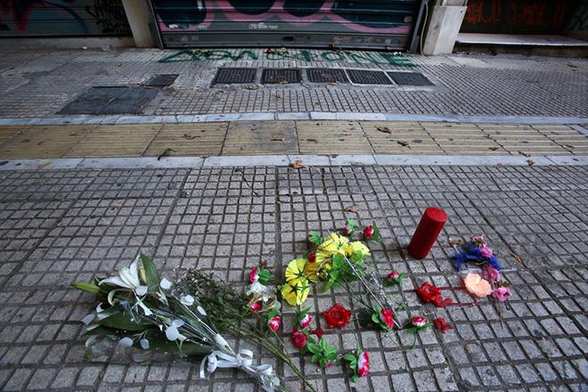 """Άγνωστοι έγραψαν τη λέξη """"Δολοφόνε"""" και συνθήματα στα ρολά, ενώ άφησαν λουλούδια έξω από το κοσμηματοπωλείο της οδού Γλάδστωνος στο κέντρο της Αθήνας, όπου βρήκε τραγικό θάνατο ο Ζακ Κωστόπουλος 33χρονος  ο οποίος υπήρξε  ακτιβιστής για τα δικαιώματα των ΛΟΑΤΚΙ, , Κυριακή 23 Σεπτεμβρίου 2018. ΑΠΕ-ΜΠΕ/ ΑΠΕ-ΜΠΕ/ ΣΥΜΕΛΑ ΠΑΝΤΖΑΡΤΖΗ"""