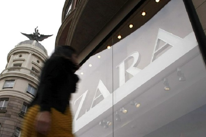 epa03987070 A woman walks past a shop window of a Zara clothing store in A Coruna, north-western Spain, 11 December 2013. According to reports, Inditex, the owner of Zara, earned net profits of 1,67 billion euros from January to September 2013, a one per cent increase on the previous year.  EPA/CABALAR