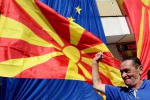 epa07025193 A participant raises his fist next to large EU (L) and the Macedonian (R) flags, during the march for European Macedonia in the center of Skopje, the Former Yugoslav Republic of Macedonia, 16 September 2018. The march is in support of the referendum scheduled for 30 September following the Prespa name agreement between Greece and FYROM (Macedonia).  EPA/NAKE BATEV
