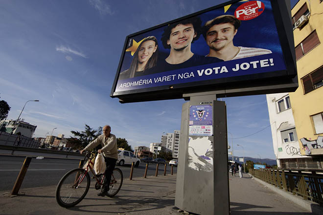 epa07054779 An Albanian man rides his bicycle near by a giant poster reading 'The future depends on your vote!' in the city of Skopje, The Former Yugoslav Republic of Macedonia, 28 September 2018. A referendum is scheduled for 30 September in Macedonia on whether to change the country's name to 'North Macedonia', to endorse a name deal to end a long running dispute between Macedonia and Greece and qualify for NATO membership.  EPA/VALDRIN XHEMAJ