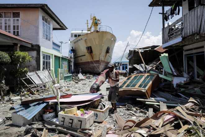 epa07063055 An Indonesian man carries his belongings past a stranded ship at a tsunami devastated area in Wani, Donggala, Central Sulawesi, Indonesia, 02 October 2018. According to reports, at least 1,234 people have died after a series of powerful earthquakes hit Central Sulawesi on 28 September 2018 and triggered a tsunami.  EPA/MAST IRHAM