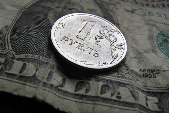 epa04531195 A Russian one Ruble coin placed on a one dollar note in Kaufbeuren, Bavaria, Germany, 16 December 2014. Russia's Central bank raised refinancing rate up to 17 per cent per a year (plus 650 basic points).  EPA/KARL-JOSEF HILDENBRAND