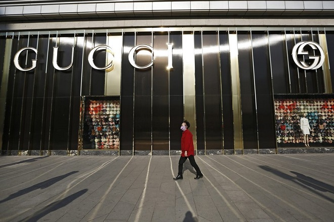 epa04749635 A woman walks past a store of luxury brand Gucci at a shopping mall in Beijing, China, 15 May 2015. A slowing economy and a government crackdown on corruption and gift-giving has affected the sales of luxury goods in China with negative one percent growth last year at approximately 115 billion RMB (16 billion euros) according to Bain & CompanyÕs 2014 China Luxury Market Study released in January 2015.  EPA/HOW HWEE YOUNG