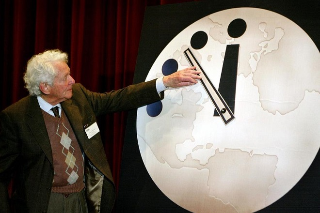 """SJO01 - 20020227 - CHICAGO, IL, UNITED STATES : Dr. Leon Lederman, an internationally renowned high-energy physicist, adjusts the hands on the """"Doomsday Clock"""" two minutes closer to midnight 27 February, 2002 at the University of Chicago. The Doomsday Clock has been used by the Bulletin of Atomic Scientist since 1947 to represent the perceived danger of a catastophic nuclear event. The clock now reads 7 minutes until midnight.      EPA PHOTO         AFPI/SCOTT OLSON/sjo/eh/ja"""