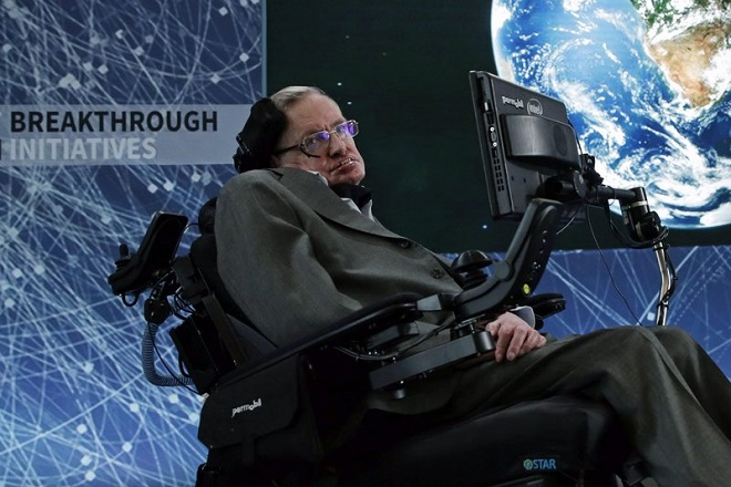 epa05255926 British scientist Stephen Hawking  (L) addresses the media while a picture of the planet Earth is shown on a video screen during a press conference on top of One World Trade Center in New York, New York, 12 April 2016. Russian billionaire Yuri Milner and Hawking announced a New Space Exploration Initiative 'Breakthrough Starshot'.  EPA/JASON SZENES