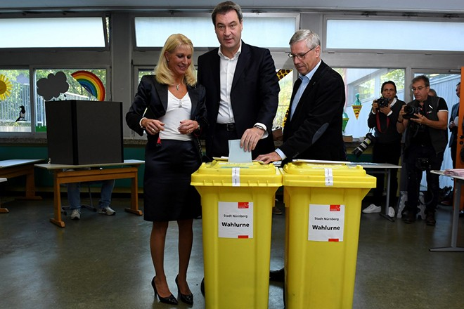 epa07092178 Bavarian Prime Minister Markus Soeder (C) casts his ballot next to his wife Karin Baumueller (L) during the Bavaria state elections at a polling station in Nuremberg (Nuernberg), Germany, 14 October 2018. According to the Bavarian state election commissioner some 9.5 million people are eligible to vote in the regional elections for a new parliament in southern German State of Bavaria. Polling official (R) is not identified.  EPA/CLEMENS BILAN