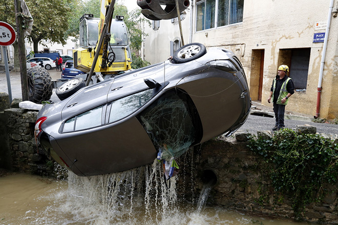 epa07094875 A man using a digger pulls a car out of water after heavy rain falls, flash floods and violent storm that hit Aude department overnight in Villegailhenc, France, 15 October 2018. According to a recent media report at least thirteen people died.  EPA/GUILLAUME HORCAJUELO