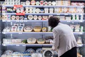 epa04971847 A woman arranges cheese products at an exhibition stand of the biennial international food fair Anuga inCologne,Germany, 10 October 2015. The range of products featured at the food fair includes vegan, gluten-free, frozen and halal food items.  EPA/MAJAHITIJ