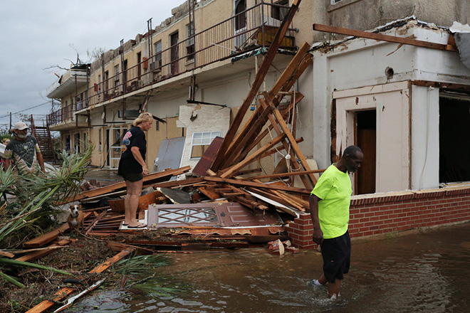 epa07084613 People walk through the wreckage of a building after the arrival of Hurricane Michael in Panama City, Florida, USA, 10 October 2018. According to media reports, Hurricane Michael made landfall on the Florida panhandle as a category 4 storm, with maximum sustained winds of up to 155 mph (200 kph). One person has died in the storm, reportedly killed by a falling tree.  EPA/DAN ANDERSON