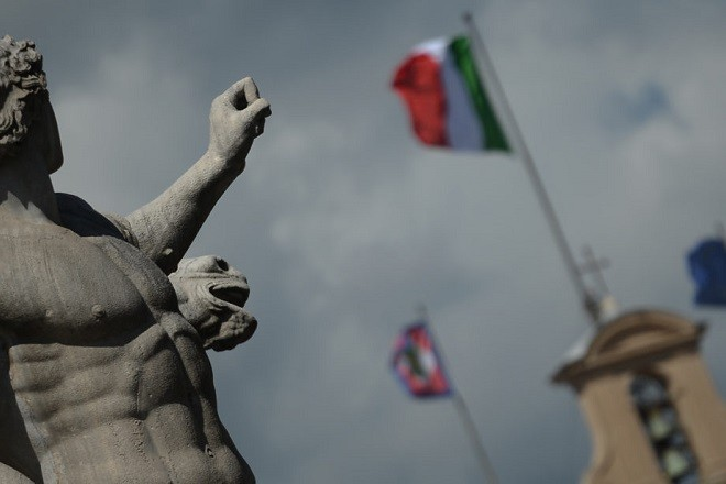 Picture of a statue in front of the Quirinale palace, Italian presidential residence, with the Italian and the European Union flag on the roof, on March 21, 2013 in Rome. Italian President Giorgio Napolitano began two days of consultations with political leaders yesterday in a bid to determine who should be given the mandate to form a new government in the eurozone's third largest economy.    AFP PHOTO / FILIPPO MONTEFORTE        (Photo credit should read FILIPPO MONTEFORTE/AFP/Getty Images)