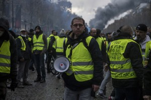 epa07187430 Protesters wearing yellow vests, as a symbol of French driver's and citizen's protest against higher fuel prices, during clashes with police on the Champs Elysee as part of a nationwide protest in Paris, France, 24 November 2018. The so-called 'gilets jaunes' (yellow vests) protest movement, which has reportedly no political affiliation, is protesting over fuel prices.  EPA/Julien de Rosa