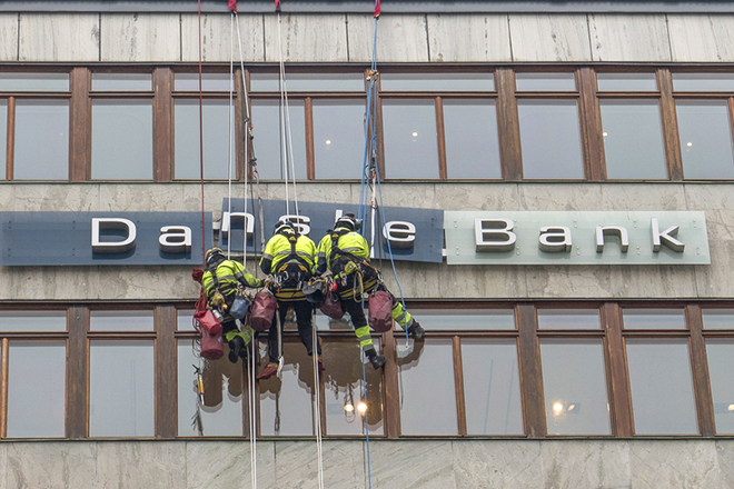 epa07036825 (FILE) - Workers maintaining the Danske Bank sign in central Stockholm, Sweden, 07 April 2016, (reissued 21 Spetember 2018. Media reports state that the Danish bank 'The Danske Bank' is in a crisis due to alleged money laundering in the bank's branch in Estonia.  EPA/LEIF BLOM  SWEDEN OUT