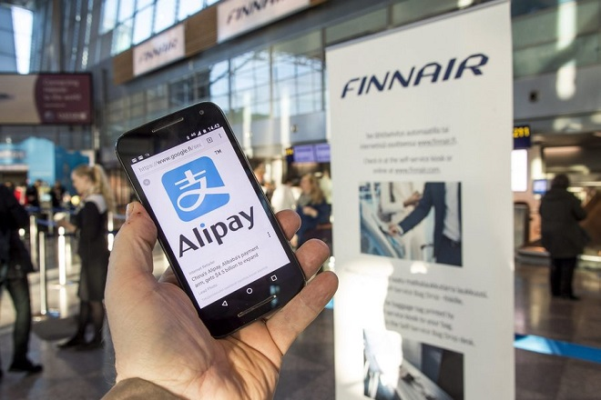 epa05754805 An Alipay-app on a smartphone screen and Finnair logos at the Helsinki airport, Finland, 27 January 2017. Finnish flag carrier Finnair said it will launch Alipay as an official method of in-flight payments for customers travelling on carrier's Asian route between Helsinki and Shanghai. Alipay is the mobile payment platform of Chinese Ant Financial. Finnair is the first airline to accept payments via Alipay.  EPA/MARKKU OJALA
