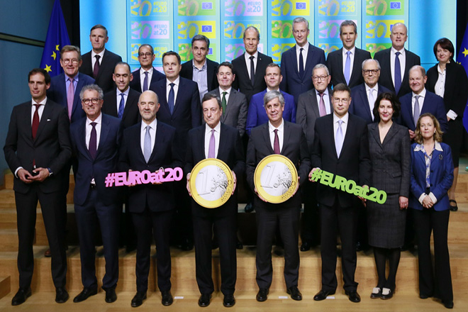 epa07206273 Eurozone finance ministers pose for a family photo during the Eurogroup Finance Ministers' meeting in Brussels, Belgium, 03 December 2018. European finance ministers gathered for a family photo to commemorate the Eurogroup's 20th anniversary. In picture are seen President of the European Central Bank (ECB) Mario Draghi (C-L) and Eurogroup President, Portuguese Finance Minister Mario Centeno (C-R) holding two large-scale replicas of a one euro coin.  EPA/STEPHANIE LECOCQ