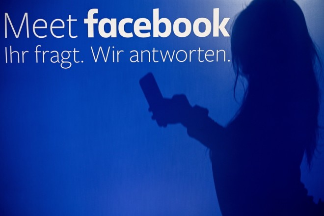 epa07170211 A shadow of a person using smartphone is cast on wall at the Facebook pop-up store in Cologne, Germany, 16 November 2018 with text reading 'Meet facebook. You ask. We answer'. The shop is open for customers from 16 to 17 November 2018. Visitors will have the opportunity to learn more about security and  privacy settings on Facebook at information booths and by talking to Facebook employees. In addition, they can try out various Facebook products and learn how to use the 'Lip Sync Live' function or create stories, for example.  EPA/SASCHA STEINBACH