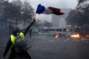 epaselect epa07202682 A protester wearing a yellow vest (gilets jaunes) waves a French flag during clashes with riot police near the Arc de Triomphe as part of a demonstration over high fuel prices on the Champs Elysee in Paris, France, 01 December 2018. The so-called 'gilets jaunes' (yellow vests) are a protest movement, which reportedly has no political affiliation, is protesting across the nation over high fuel prices.  EPA/YOAN VALAT