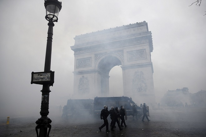 epaselect epa07202665 French riot police pass by the Arc de Triomphe as they clash with protesters wearing yellow vests (gilets jaunes) during a demonstration over high fuel prices on the Champs Elysee in Paris, France, 01 December 2018. The so-called 'gilets jaunes' (yellow vests) are a protest movement, which reportedly has no political affiliation, is protesting across the nation over high fuel prices.  EPA/YOAN VALAT