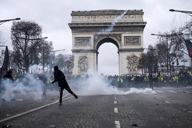 epa07216936 A Yellow Vests protester hurls an object to police forces during a demonstration in Paris, France, 08 December 2018. Police in Paris is preparing for another weekend of protests of the so-called 'gilets jaunes' (yellow vests) protest movement. Recent demonstrations of the movement, which reportedly has no political affiliation, had turned violent and caused authorities to close some landmark sites in Paris this weekend.  EPA/JULIEN DE ROSA