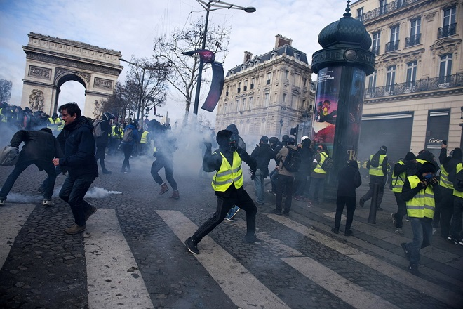 epa07216939 A Yellow Vests protester hurls an object to police forces during a demonstration in Paris, France, 08 December 2018. Police in Paris is preparing for another weekend of protests of the so-called 'gilets jaunes' (yellow vests) protest movement. Recent demonstrations of the movement, which reportedly has no political affiliation, had turned violent and caused authorities to close some landmark sites in Paris this weekend.  EPA/JULIEN DE ROSA