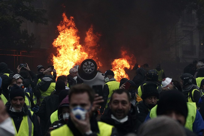 epa07206136 Cars burn as protesters wearing yellow vests (gilets jaunes) clash with riot police near the Arc de Triomphe as part of a demonstration over high fuel prices on the Champs Elysee in Paris, France, 01 December 2018 (issued on 03 December 2018). The so-called 'gilets jaunes' (yellow vests) protest movement, which reportedly has no political affiliation, is protesting across the nation over high fuel prices. According to reports, the damage left after the riots in Paris are estimated to exceed three to four million euro.  EPA/YOAN VALAT