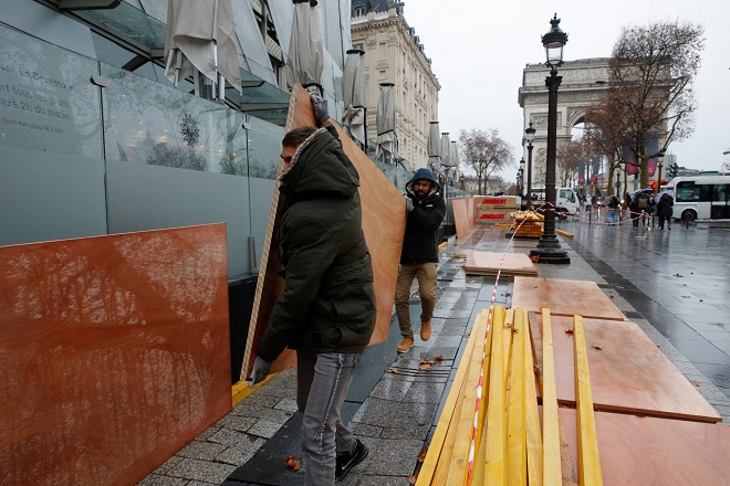 "Workers protect a shop window with wood panels on the Champs-Elysees Avenue near the Arc de Triomphe on the eve of a ""yellow vests"" protest in Paris, France, December 7, 2018. REUTERS/Philippe Wojazer"