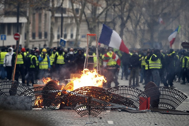 epaselect epa07217472 Yellow Vests (Gilets jaunes) protesters set barricades on fire in the street during clashes with French police forces as part of a demonstration near the Champs Elysees in Paris, France, 08 December 2018. The so-called 'gilets jaunes' (yellow vests) is a protest movement, which reportedly has no political affiliation, that continues protests across the nation over high fuel prices.  EPA/IAN LANGSDON