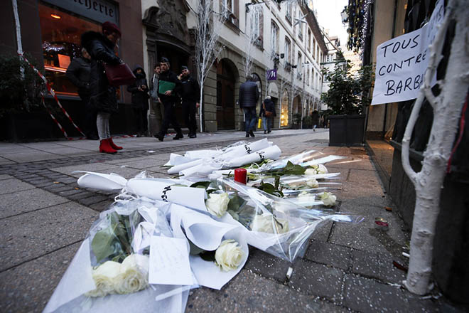 epa07226058 Inhabitants and police officers look at candles, flowers and a sign reading 'All united against barbarity' which are left where a person was killed during the Christmas Market shooting in Strasbourg, France, 12 December 2018. According to latest reports, three people were killed and several injured when a gunman opened fire at the Strasbourg Christmas market a day earlier. The suspect is reported to be at large and the motive for the attack is still unclear.  EPA/RONALD WITTEK