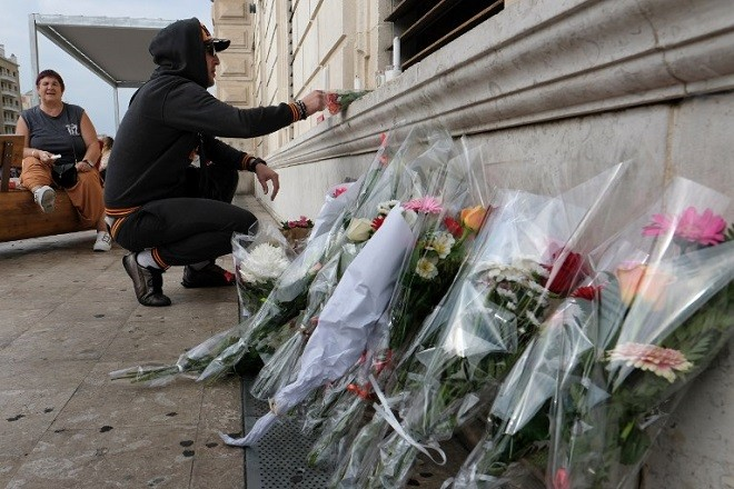 A man lights a candle at a makeshift memorial set-up on  October 2, 2017 outside Saint-Charles train station in Marseille, where two students, two 20-year-old cousins, were killed the day before by an Islamist knifeman who was shot dead by soldiers. The man who stabbed two young women to death in Marseille in an attack claimed by the Islamic State group used seven different identities and had been arrested just days earlier, French prosecutors said. France has been under a state of emergency since the IS gun and bomb attacks in Paris in November 2015 -- part of a string of jihadist assaults that have left more than 240 people dead over the past two years. / AFP PHOTO / BORIS HORVAT