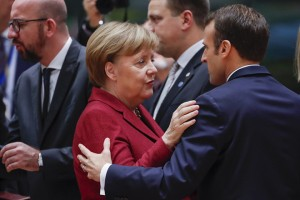 epa07228607 German Federal Chancellor Angela Merkel (C) and French President Emmanuel Macron (R) greet each other prior to the start of the European Council in Brussels, Belgium, 13 December 2018. During their two days summit, European leaders will focus on  the 'Brexit' and on the EU's budget for 2021until 2027. The Summit will resume on 14 December with the EU28 adoption of the conclusions on the Single Market, climate change, migration, disinformation, the fight against racism and xenophobia, and citizens' consultations.  EPA/OLIVIER HOSLET