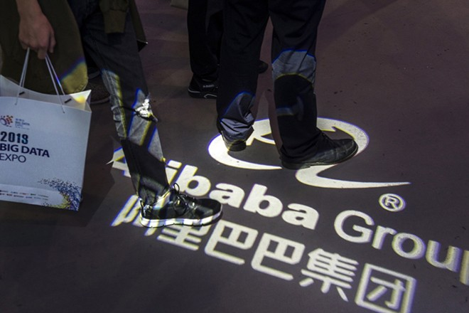 epa06769354 People walks on top of the Alibaba Group logo in front of their booth on Big Data expo in Guiyang, Guizhou Province, China, 28 May 2018. Big Data Industry Expo 2018 opened in Guiyang, which according to reports shall become the technical support center and Internet Content Provider (ICP) filing center for Alibaba Cloud, the cloud service of Chinese e-commerce giant Alibaba. All websites hosted on the Chinese mainland must be ICP filed with the Ministry of Industry and Information Technology. A website cannot direct to any server located on the Chinese mainland for public visits until the developer get an ICP filing number. Alibaba Cloud will also provide cloud storage service for the research data of China's 500-metres-aperture Spherical Radio Telescope in Guizhou Province, the world's largest single-dish radio telescope.  EPA/Aleksandar Plavevski