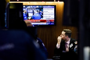 epa07237759 A trader looks at financial news at the end of the trading day at the New York Stock Exchange in New York, New York, USA, on 17 December 2018. The Dow closed the day down over 500 points after falling over 600 earlier.  EPA/JUSTIN LANE