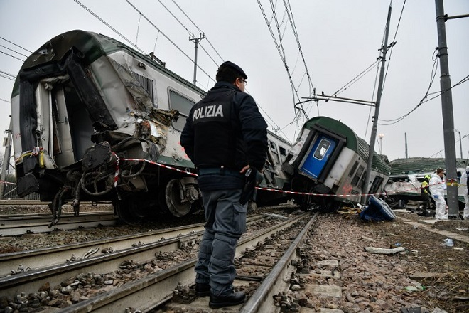 Italian policemen work on the site of a train derailment on January 25, 2018 in Pioltello, near Milan.  At least three people were killed and 10 seriously injured when a packed regional train derailed near Milan in northern Italy, emergency services said. The incident happened at around 7 am (0600 GMT) near the Milan suburb of Segrate. The cause was not immediately clear. / AFP PHOTO / Piero CRUCIATTI