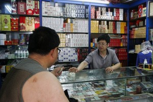 epa04778386 A vendor of cigarettes, drinks and snacks receives payment from a customer at his store in Beijing, China, 01 June 2015. Beijing is implementing a new smoking ban starting 01 June in efforts to curb smoking in public and work places and indoor areas of commercial establishments.  EPA/ROLEX DELA PENA
